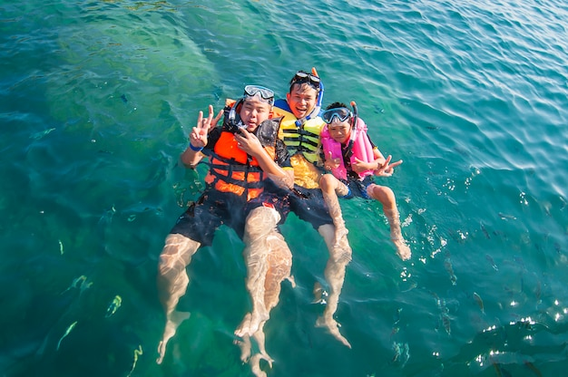 Three guys floating happily in the sea water Free Photo