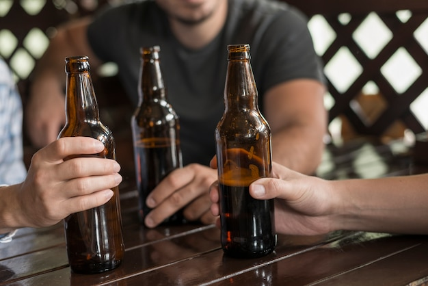 Three hands with beer bottles on table Free Photo