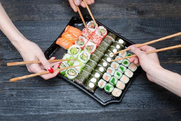Three hands with chopsticks and sushi set. Premium Photo