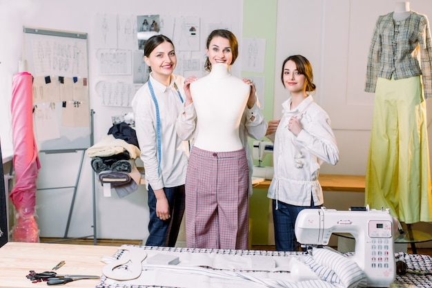 Three Happy Fashion Designers Working With Fabric Clothing Sketches Measuring Materials On Mannequin At The Studio Full Of Tailoring Tools And Equipment Premium Photo