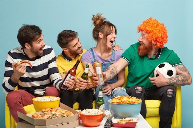 3人の幸せな友達がかつらで面白いひげを生やした男を見て、ビールのボトルをチリンと鳴らし、ピザを食べ、テレビでサッカーの試合を見ながら楽しんでください 無料写真