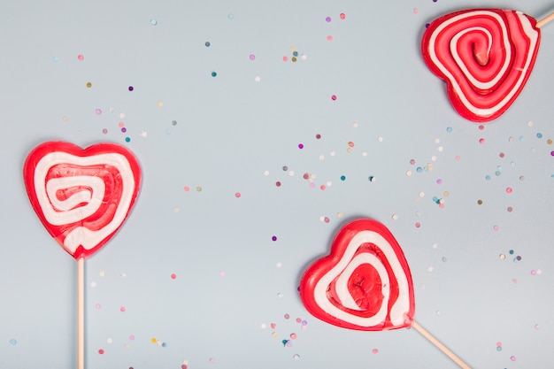 Three heart shape red lollipops on gray background with colorful