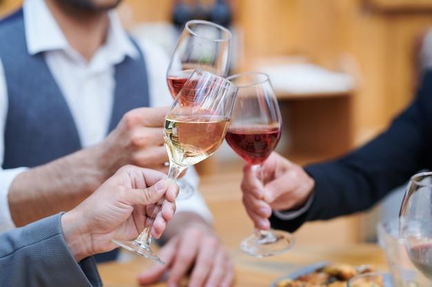 Трое людей звенят бокалами с разными сортами вина во время праздничного тоста Premium Фотографии