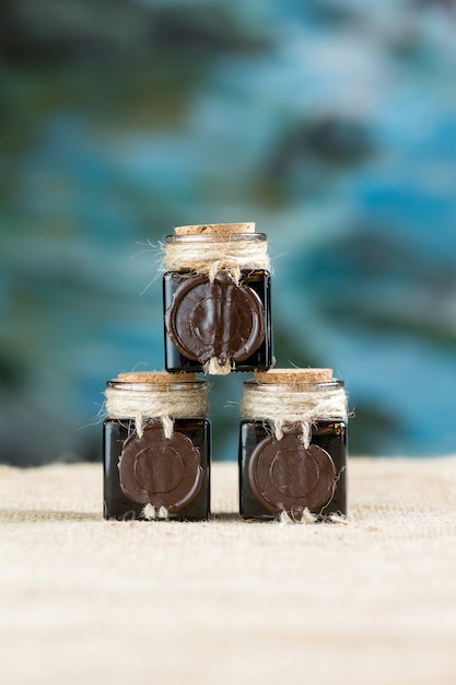 Three ink bottles, mummy,  in jars with wax Premium Photo