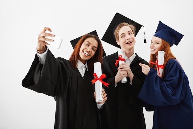 Трое иностранных выпускников друзей, радуясь в мантии, делая selfie на телефоне. будущие специалисты весело проводят время со своими дипломами. Бесплатные Фотографии