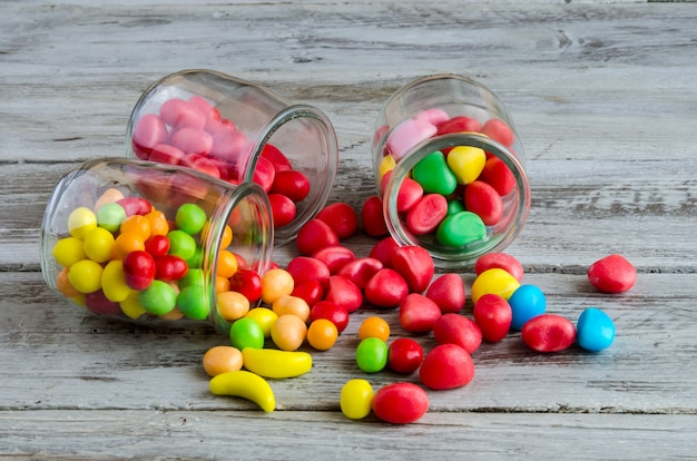 Three jars on table with scattered candies Premium Photo