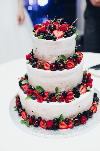Three-layered wedding cake with fresh berries.decorated with strawberry, blueberry, cherry and blackberry. Premium Photo