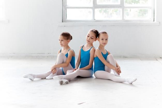 Три маленькие балетные девушки сидят и позируют вместе Бесплатные Фотографии