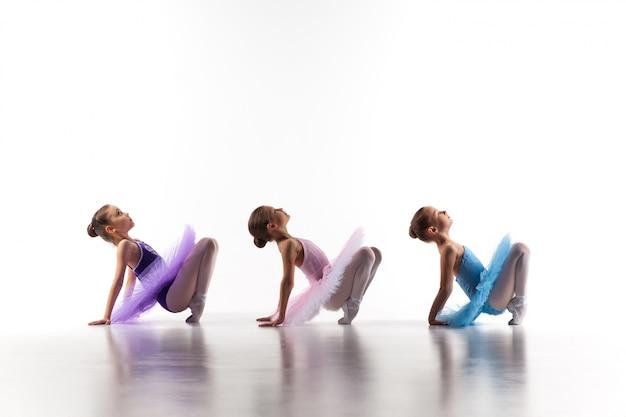 チュチュに座っていると一緒にポーズ3つの小さなバレエ少女 無料写真