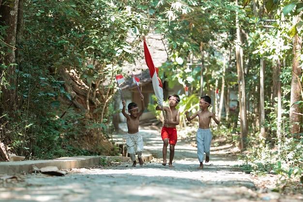 Три маленьких мальчика бегут без одежды, держа в руках красно-белый флаг и поднятые Premium Фотографии