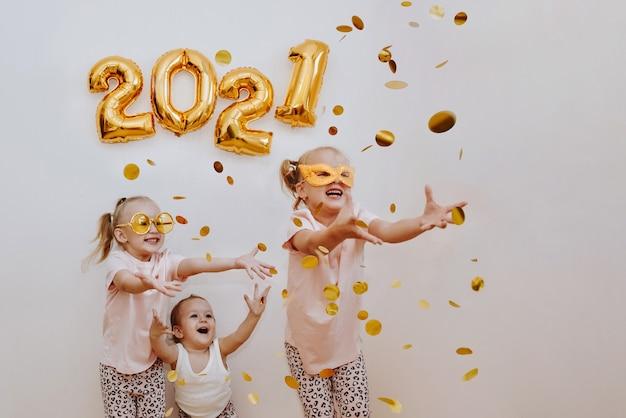 세 어린 소녀는 비행 황금 색종이를 즐기고있다 프리미엄 사진