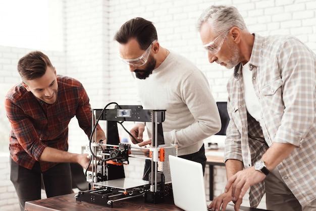 Three men set up a self-made 3d printer . Premium Photo