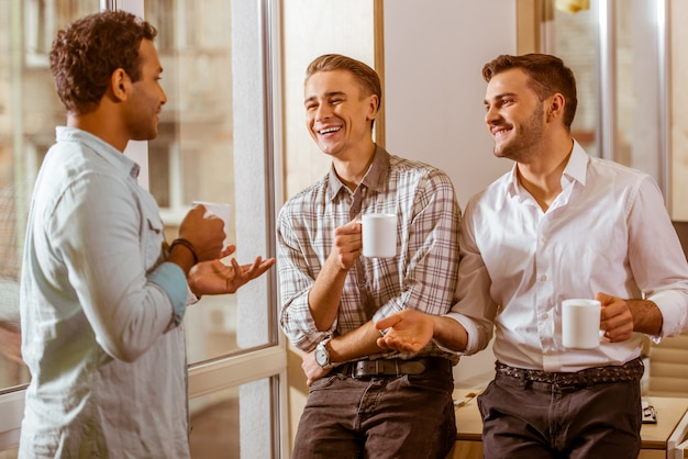 Three men stand in the office and discuss the business idea. Premium Photo