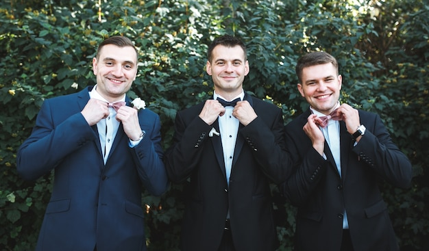 Three men in suits posing in garden Free Photo