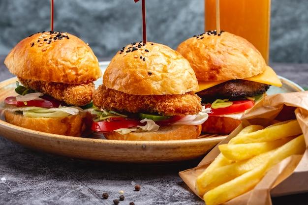 Piatto da tre mini hamburger servito con patatine fritte in scatola di carta Foto Gratuite