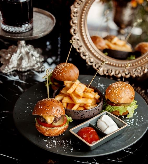 Tre mini hamburger serviti con patatine fritte, pomodoro e maionese Foto Gratuite
