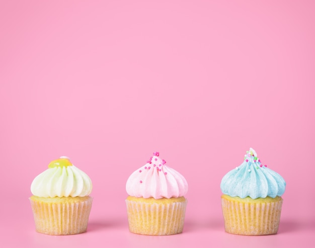 Three mini pastel cupcakes on pink copy space Premium Photo