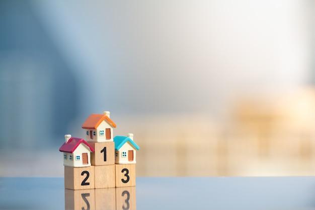 Three miniature houses on winner podium on modern cityscape background Premium Photo