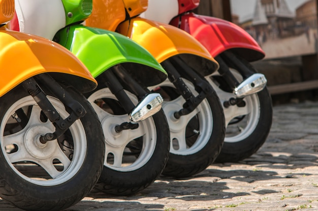 Three mopeds painted in red green yellow colors Premium Photo
