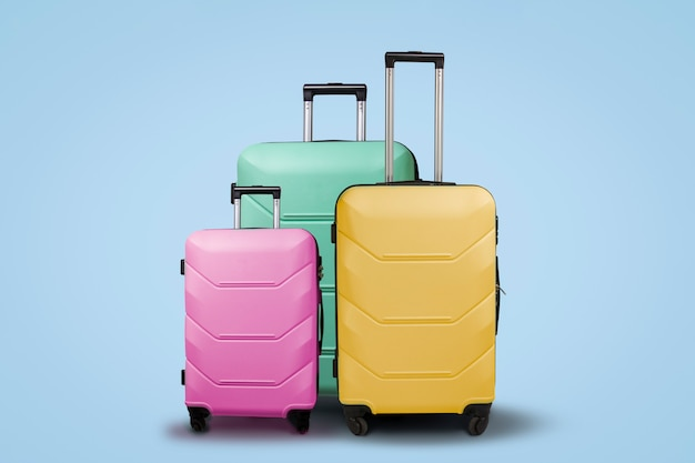 Three multi-colored plastic suitcases on wheels on a blue background. travel concept, vacation trip, visit to relatives Premium Photo