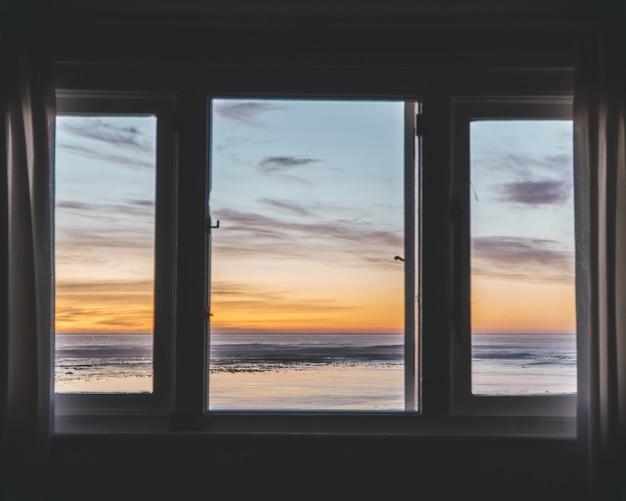 Окно из трех панелей с прекрасным видом на закат снаружи Бесплатные Фотографии