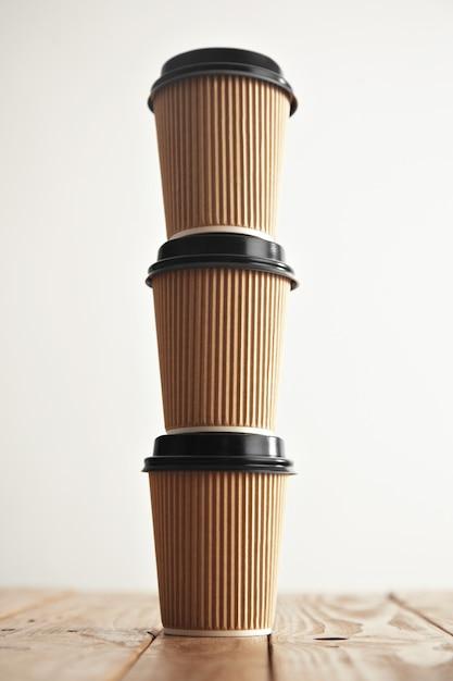 白で隔離の素朴なヴィンテージテーブルの列に立っている黒いキャップと3つのペーパークラフトカップ 無料写真