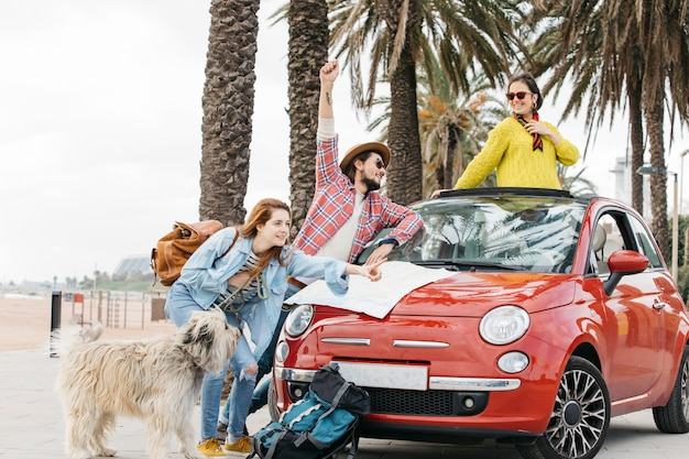Three people and dog standing near car with road map Free Photo
