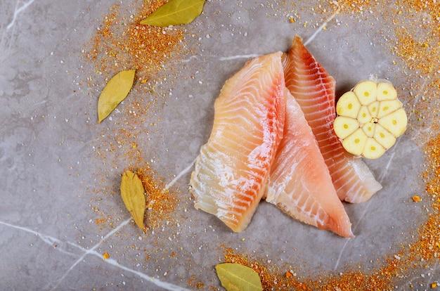 Three pieces of fresh tilapia on marble board Premium Photo