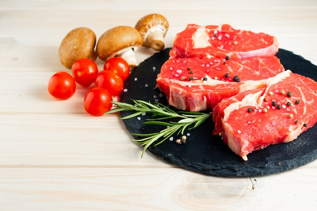 Three pieces of juicy raw beef on a stone cutting board on a white wooden table Premium Photo