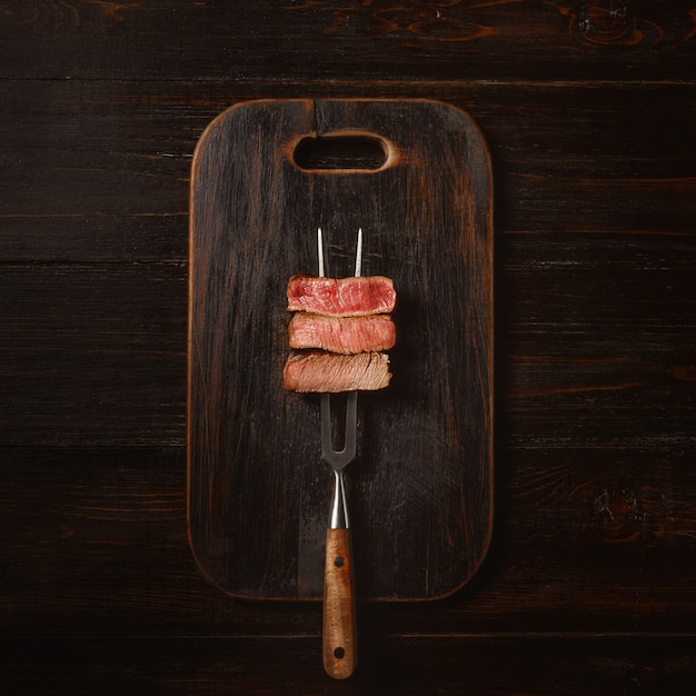 Three pieces of meat on a fork for meat. three types of meat roasting, rare, medium,well done. Premium Photo