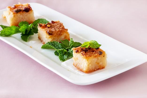 Три пирожные basbousa или namoora традиционный арабский десерт. очень вкусный домодельный торт манной крупы с гайками на белой плите. Premium Фотографии