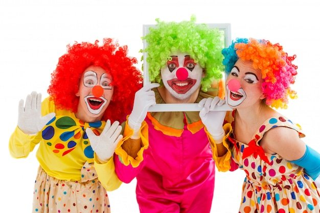 Three playful clowns holding making funny faces. Premium Photo