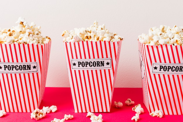 Three popcorn box filled with popcorns on pink background Free Photo