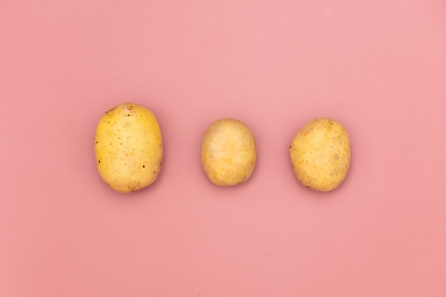 Three potatoes on pink background Premium Photo