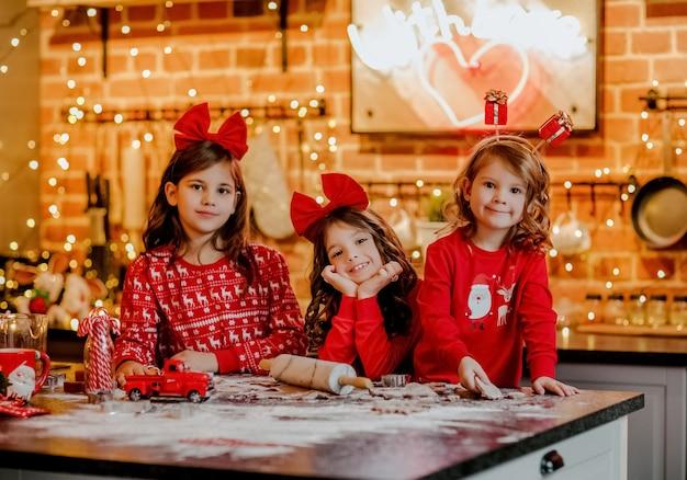 クリスマスの背景を持つキッチンでクッキーを作る赤いクリスマスのパジャマとヘッドバンドの3人のかわいい若い女の子。 Premium写真