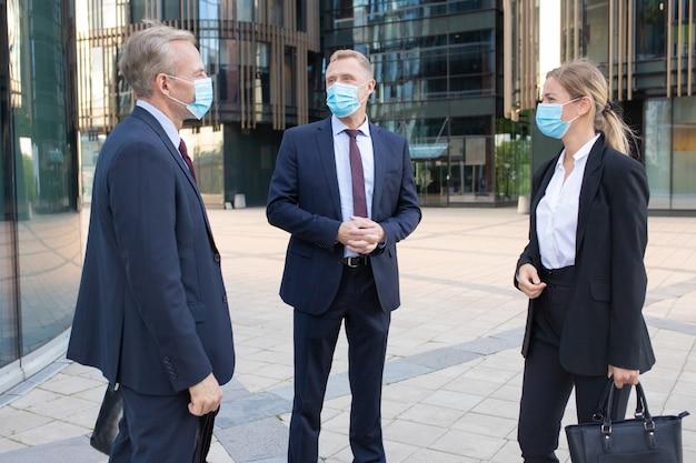 Tre colleghi di lavoro professionisti in maschere facciali discutendo affare al di fuori. contenuti manager di successo in piedi per strada e parlando di lavoro. negoziazione, protezione e concetto di partenariato Foto Gratuite