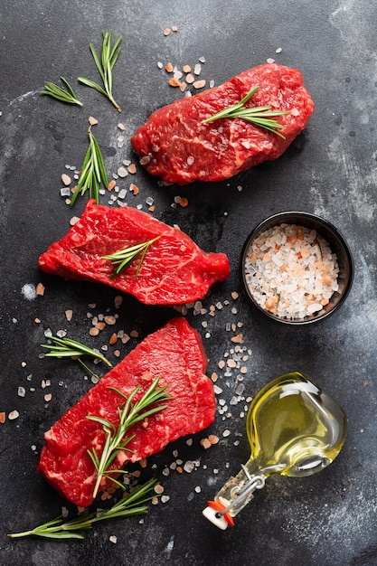 Three raw beef steak with spices, onions and rosemary on dark slate or concrete background. top view Premium Photo