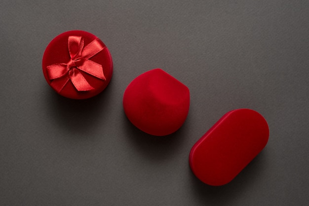 Three red closed jewelry boxes on a black background. Premium Photo