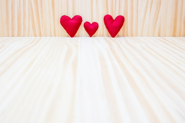 Three red hearts on a wooden background for valentine's day Premium Photo