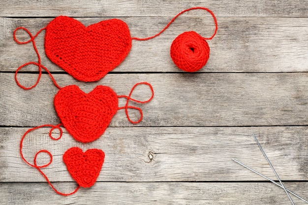 Three red knitted hearts on a gray wooden background Premium Photo