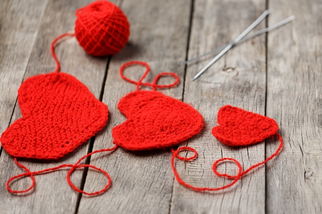Three red knitted hearts, symbolizing love and family. family relationship, bonds. Premium Photo