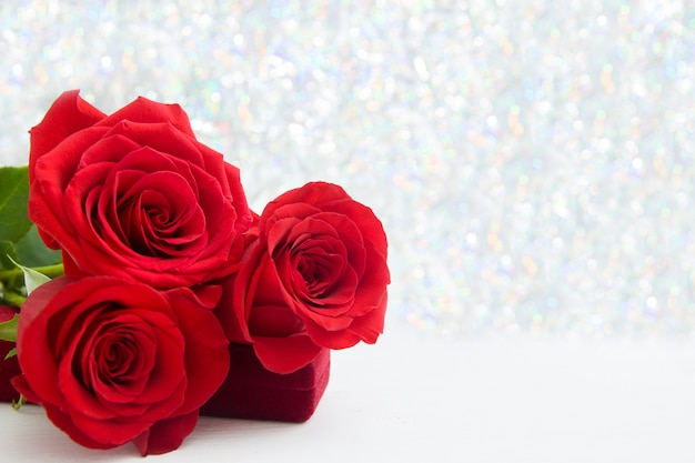 Three red roses and jewelery present box with boke background Premium Photo