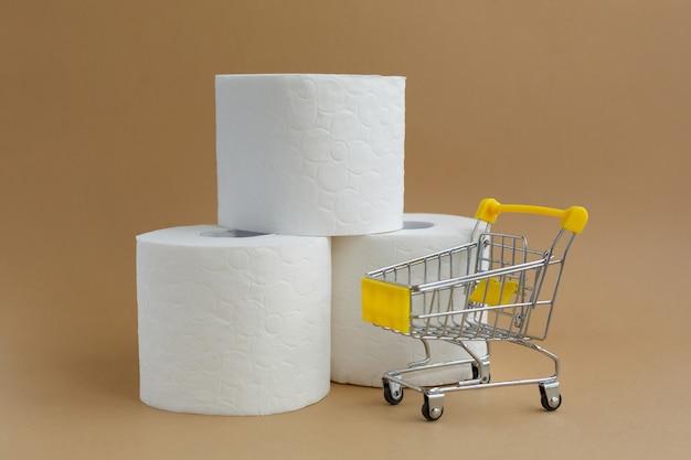 흰색 배경 및 작은 식료품 카트에 흰색 화장지 3 롤 프리미엄 사진