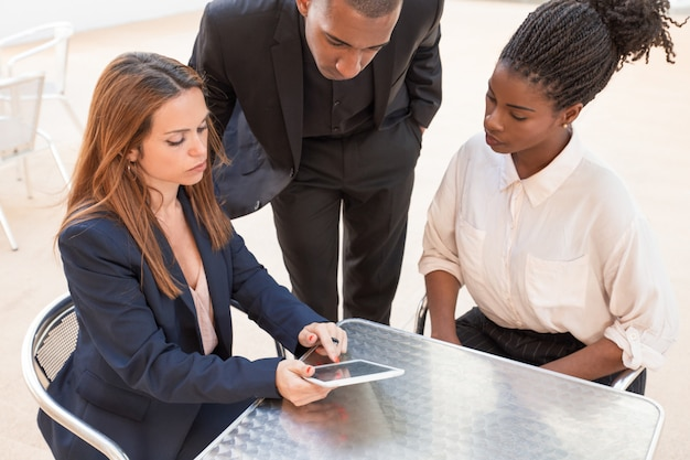 Three serious young businesspeople watching data on pc tablet Free Photo