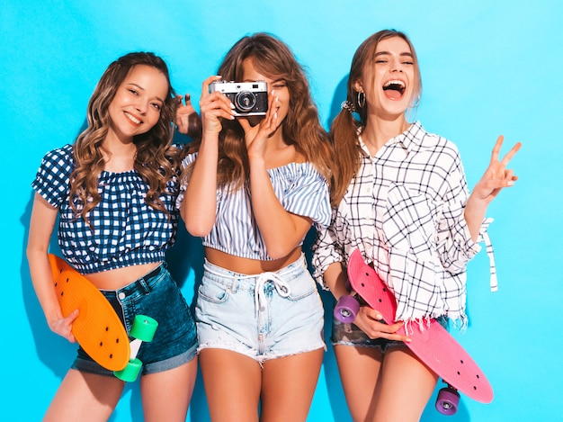 Three sexy beautiful stylish smiling girls with colorful penny skateboards. women in summer checkered shirt clothes posing. models taking pictures on retro photo camera Free Photo