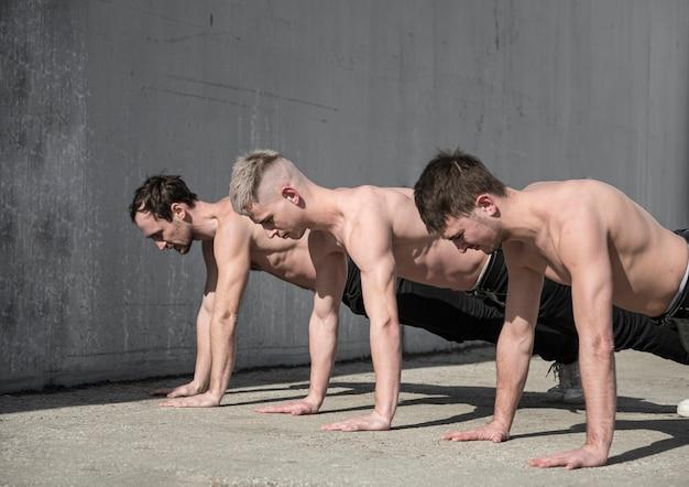 Три танцора хип-хопа без рубашки репетируют на улице Бесплатные Фотографии