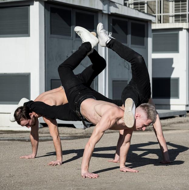 Три хип-хоп исполнителей без рубашки танцуют на улице Бесплатные Фотографии