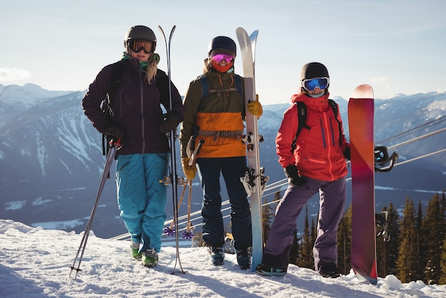 Three skiers with skies standing on snowy landscape Free Photo