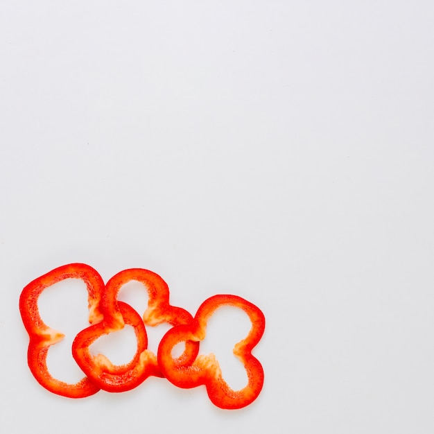Three slices of red bell pepper on the corner of the white background Free Photo