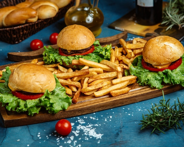 Three small beef burgers and french fries served on wooden board Free Photo